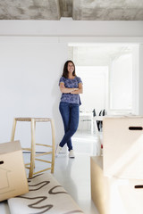 Happy woman with arms crossed leaning on wall in new home