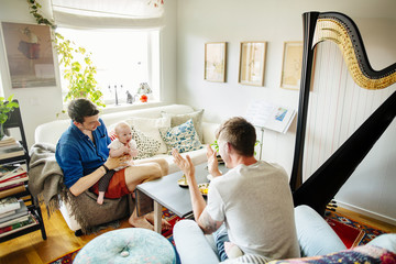 Two men playing with baby girl in living room