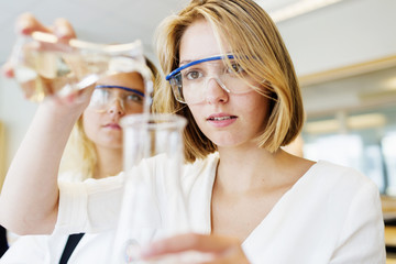 Young university student performing science experiment in laboratory