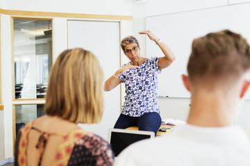 Mature female professor teaching students in classroom