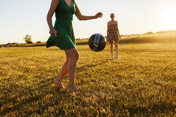 Women playing soccer in field
