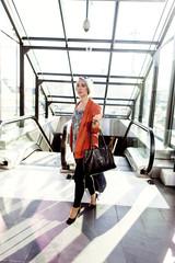 Businesswoman walking by escalator at railroad station