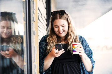 Smiling businesswoman using smart phone while holding coffee cup outdoors