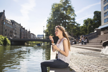 Side view of young woman having ice cream by canal
