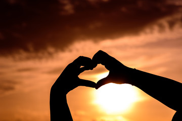 Concept or conceptual heart shape or symbol made of human or woman and man hand silhouette over a sky at sunset background for love, valentine, romantic, couple, wedding, romance, summer or sunrise