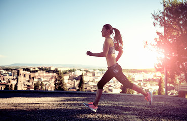 Running athletic female exercising at sunset outdoors. Concept of sport, fitness and lifestyle.
