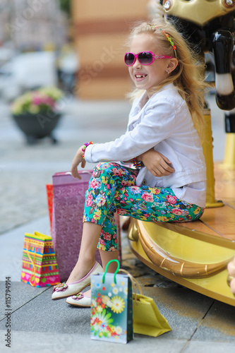 1aca1b03b Child On Old French carousel in a holiday park. Elegant Charming cute little  girl in fashionable clothes and sunglasses enjoys, sitting with full  shopping ...