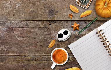 halloween concept, coffee, notebook and pumpkin on old woodeb table background, high contrast