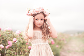 Summer portrait of baby girl wearing trendy dress and hairstyle with roses outdoors. Looking at camera.