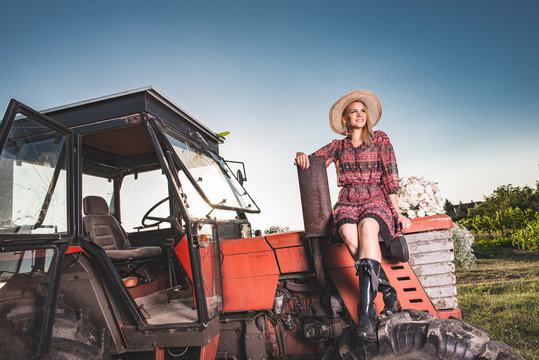 Young farmer woman posing on red, old tractor.