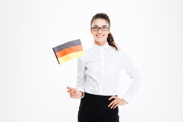 Smiling pretty young businesswoman standing and holding flag of Germany
