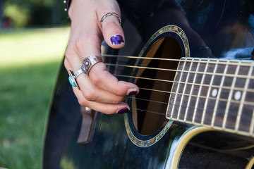 Girl playing guitar in the park in summer. The image is the foreground and fingers and hands are touching the strings of the blue guitar. She is sitting on the grass.