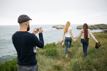 Man with beard taking a picture with a mobile to two girls