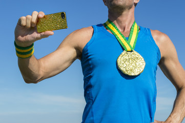 Brazilian gold medal athlete standing against blue sky using his mobile phone to take a photo