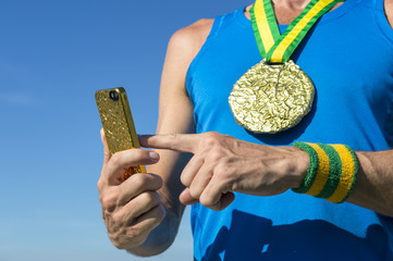 Brazilian gold medal athlete with green and yellow Brazil color wristbands using mobile phone against blue sky