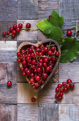 Red currants in bowl in the heart shape on a vintage wooden back