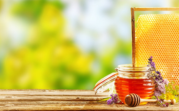 Jar of fresh honey with flowers and honeycomb