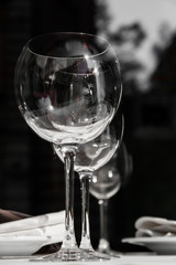 Wine goblets in the shadows in perspective with reflection in bl