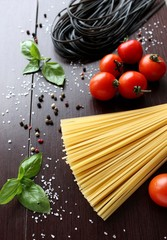 Ingredients for cooking pasta with tomato, black pasta, herbs, spices.