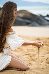 Girl playing sand in her hands in the beach