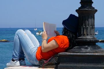 rilassarsi in riva al mare leggendo un libro