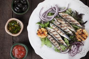 Grilled sardine fish with lettuce and onion