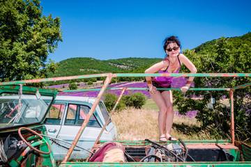 Femme en short dans une casse de vieilles voitures en Provence