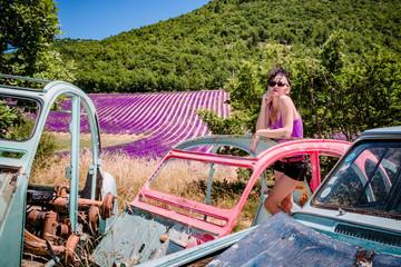 Femme en short dans une casse de vieilles voitures devant les champs de lavandes, en Provence