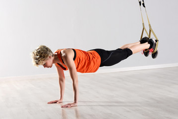 Woman balancing on floor with ropes around legs