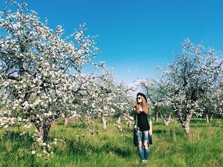девушка гуляет в яблоневом цветущем саду