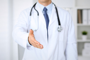 Male medicine doctor offering helping hand  for  handshake. Partnership and trust concept.