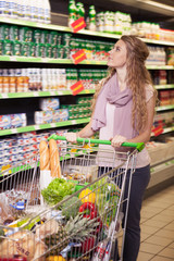 Young woman shopping and choosing goods at the supermarket