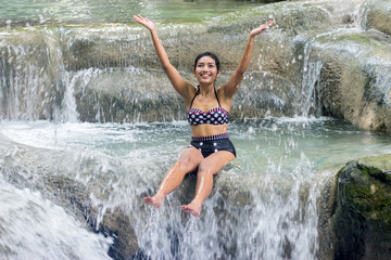 woman in retro swimsuit playful in a waterfall