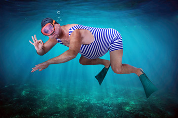 diver in retro swimsuit shows gesture O.K. under water
