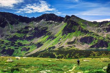Lone hiker walks among the mountains