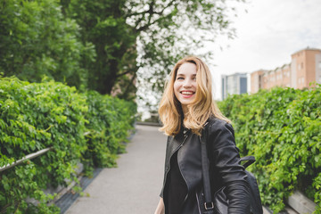 Portrait of young beautiful caucasian blonde hair woman outdoor in a city park walking and turning overlooking smiling - happiness, carefree, having fun concept