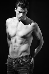 Shirtless muscular man in jeans in black and white