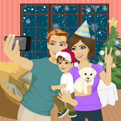 Smiling mother, father and little son making selfie with camera over living room and christmas tree background