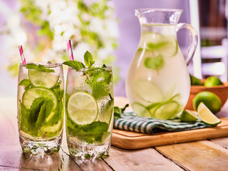 Country drink. On wooden boards is glass jug and two glasse with transparent drink and lime glue bowl. A drink number hundred seventy three with ice cubes . Country life. Light background.