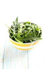 Fresh arugula leafs on a blue wooden table