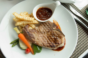 steak with pepper sauce on a plate together with vegetable