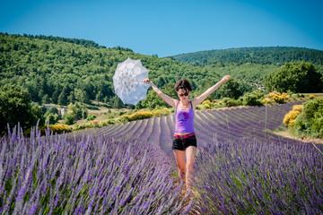 Femme en short et son ombrelle dans un champ de lavandes en Provence