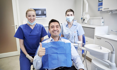 happy female dentists with man patient at clinic
