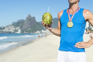 Gold medal gay athlete standing with a coco gelado green coconut on Ipanema Beach in Rio de Janeiro, Brazil