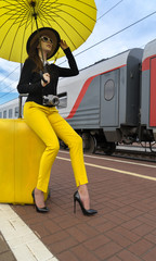 At the train station, the girl with a yellow suitcase and the camera waits for the train