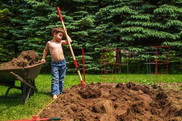Boy taking a break from digging the garden