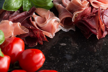 Jambon mix. Ham. Traditional Italian and Spanish salting, smoking, dry-cured dish - jamon Serrano and prosciutto crudo sliced with herbs and tomatoes on dark stone background. Copy space. Closeup.