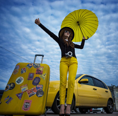 The girl stops the car with luggage