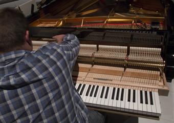 man tunes a piano
