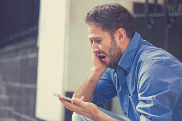 Desperate sad young man looking at bad text message on his mobile phone